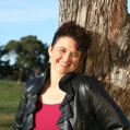 Liz Hamill wearing a red top and a black leather jacket in the sunshine leaning against a tree