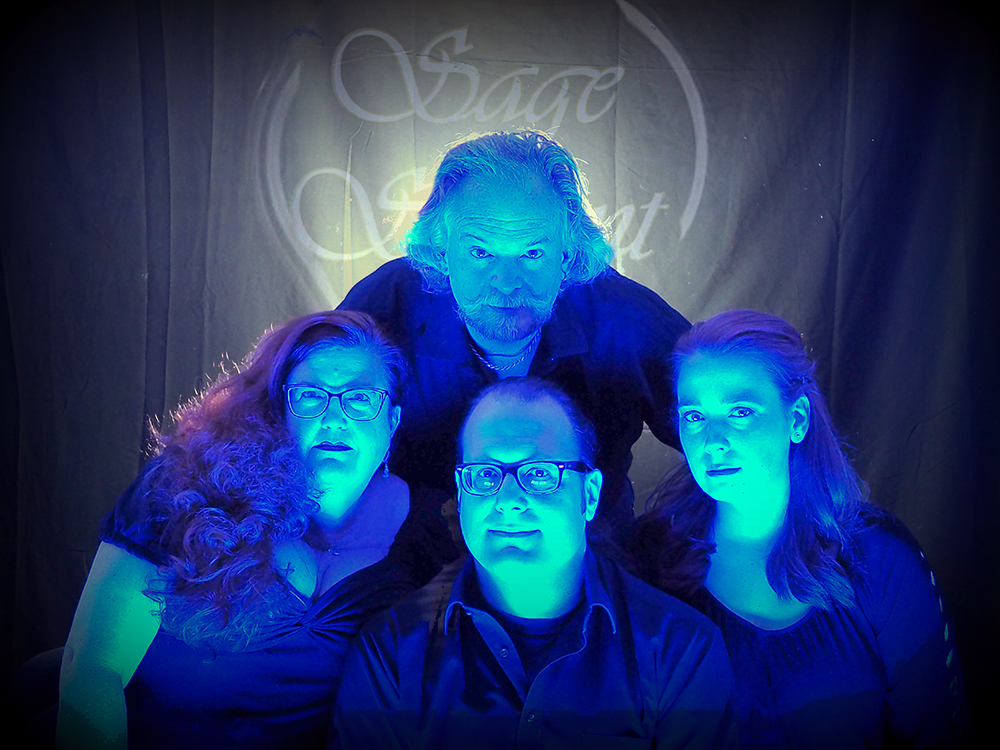 Sage & Savant; four people dressed in black and lit with bright blue lights look straight into the camera