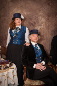 Sage & Savant's Chip and Eddie Clark; a man seated with a woman standing behind him her hand on his shoulder. They both wear formal clothes in blue silk and black velvet and short top hats