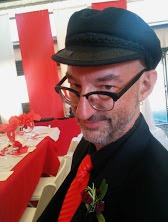 Author Chaz Brenchley in a black button down with a bright red tie, wearing a cabbie hat and black rimmed glasses looking off to the left side of the image