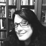A black and white image of the author Christine Cianci wearing black rectangular glasses and standing in front of a library of books.