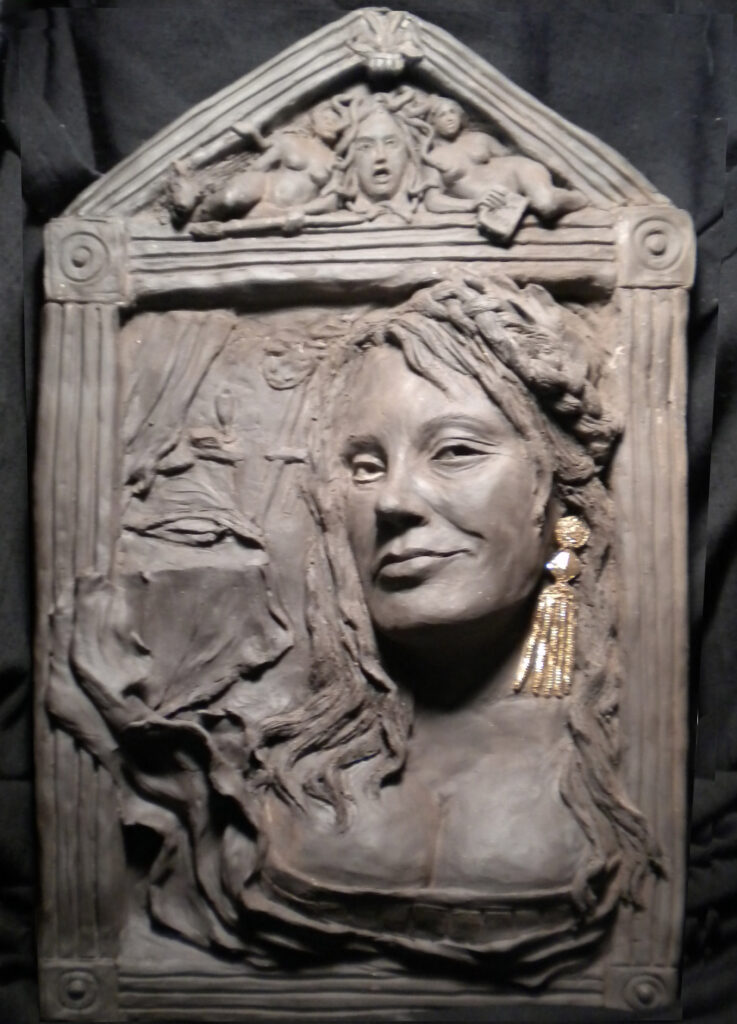 A clay portrait of the author with flowers a Roman style with a low cut dress, hair flowing loose with a braided circlet, large gilded earrings, framed with Doric columns and a cherubic head in a triangular section overhead.